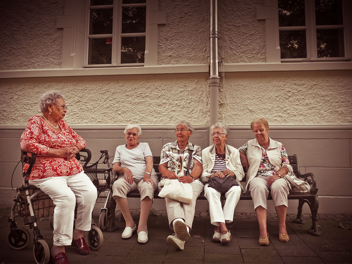 Old ladies sitting in front of a nursing home